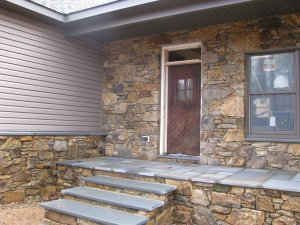 Front of home finished with real stone veneer from on-site